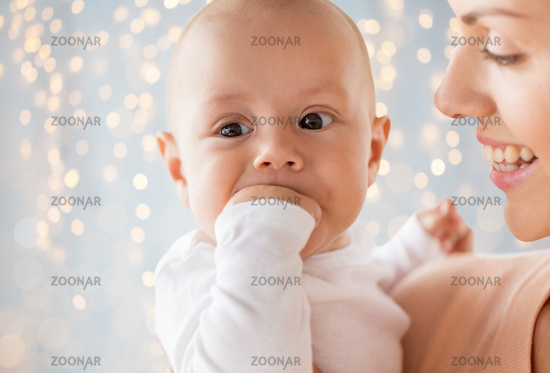 happy mother with baby sucking fingers over lights