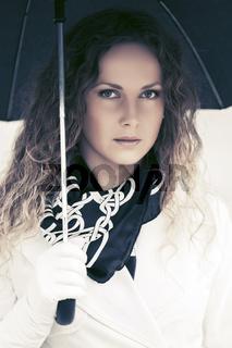 Beautiful fashion woman with umbrella walking in city street