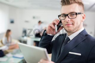 Junger Entrepreneur telefoniert mit Smartphone