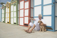 Colorful beach huts and senior man with dog