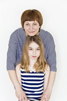 Beautiful mother and daughter on white