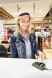 Junge Frau zahlt mit Kreditkarte an der Kasse