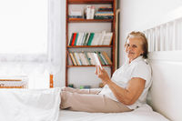 Elderly woman sitting comfortably on bed and using her digital tablet