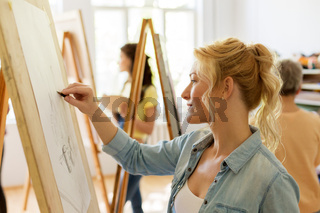 woman with easel drawing at art school studio