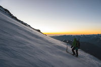 climber at sunrise early morning walks on the slope and on the ground above the snow sweeps drifting snow