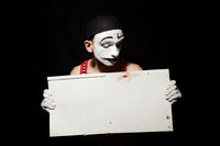 Portrait of sad mime holding white paper dirty sheet in hands.  Studio photo on a black background