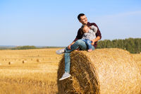 Happy father and two year old girl sitting on hay bale in harvested field