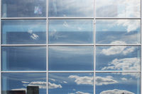Reflection of the sky with clouds in the windows of a major business center in the summer.