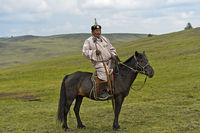 Älterer Nomade in traditioneller Kleidung reitet auf einem Pferd in der Steppe