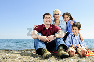 Happy family sitting at beach