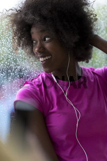 portrait of young afro american woman in gym while listening music