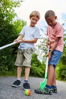 Zwei Jungen spielen zusammen Straßenhockey