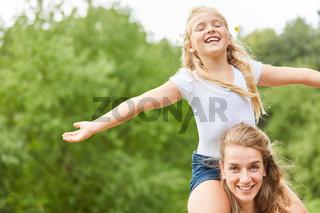 Mädchen sitzt auf dem Rücken der Mutter