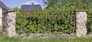 Fragment of the village fence. Made of whole granite stones and steel grating.