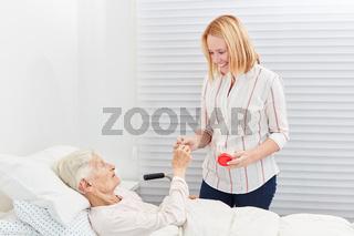Frau gibt kranker Seniorin im Bett eine Tablette