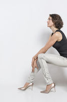 Frau wartet sitzend auf einem Hocker