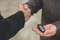 Vehicle dealer passing keys from new car to happy young man.