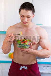 Junger Mann isst essen Salat Bodybuilding Bodybuilder gesunde Ernährung Hochformat vegan