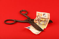 Scissors cut Euro banknote over red background