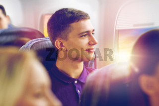 happy young man travelling by plane