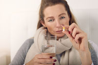 Sick woman holding a glass of water and a pill