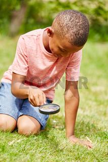 Junge als Detektiv mit Lupe