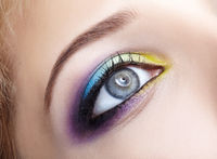 Closeup macro image of human female eye with violet, blue and and yellow makeup