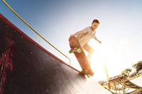 Teen skater hang up over a ramp on a skateboard in a skate park