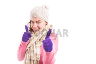 Young woman wearing cozy knitted clothes showing double like