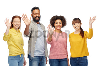 international group of happy people waving hands