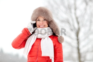 happy woman in winter hat calling on smartphone