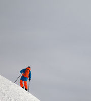 Skier before downhill on snowy freeride slope and misty sky