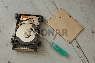 Broken and Destroyed Hard Drive Disk and Tools on Wooden Table