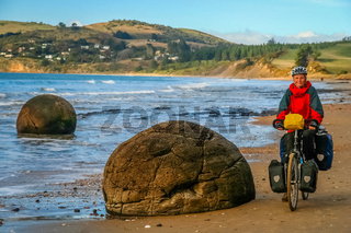 Cycle tourer on the New Zealand beach