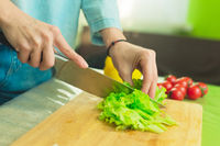 Hands of a young girl slice green lettuce leaves on a wooden cutting board on a green table in a home setting against a background of red cherry tomatoes.