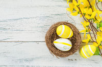 An easter nest with yellow easter eggs on a wooden background