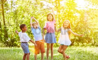 Gruppe Kinder beim Jubeln und Tanzen im Sommer