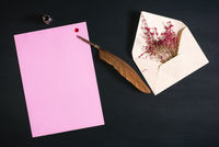 Quill pen on a blank paper sheet and flowers
