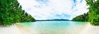 Idyllic tropical clear sea and green island panorama