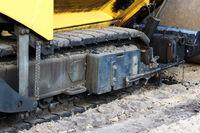 mini asphalt paver is near the road repair site. Russia.
