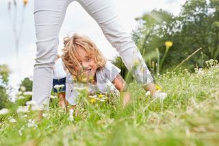 Blonder Junge spielt glücklich im Gras