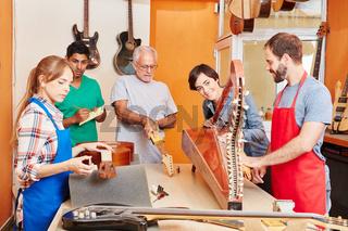 Gitarrenbauer und Lehrlinge in der Werkstatt