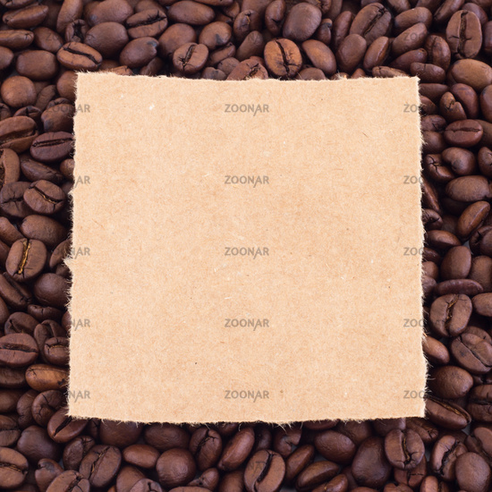 Square frame of coffee beans and rustic teared paper centered