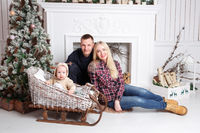 Happy family at Christmas. The parents and the baby sitting on the floor and smiling.