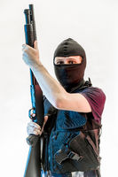 Thief, man armed with balaclava and bulletproof vest, gun and shotgun, kalashnikov