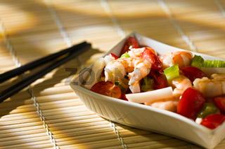 Shrimp salad over a bamboo tablecloth and chopsticks