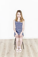 Teenager girl are sitting on stool in striped clothes