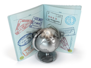 Passport with lot of visa stamps and metal globe isolated on white background. Travel and tourism concept.