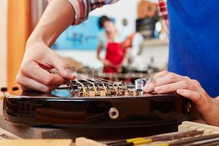 Gitarrenbauer justiert Gitarrensaite von E-Gitarre