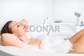 Young woman enjoying bathing in bathtub